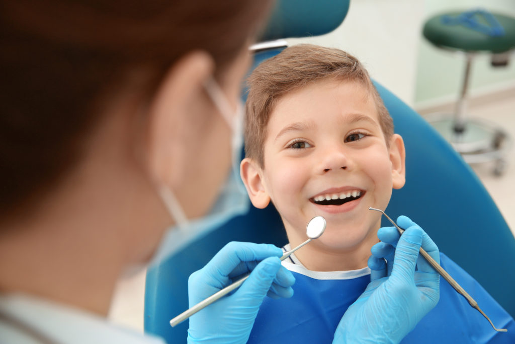 Pediatric Dentist examining little boy's teeth in clinic